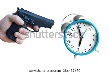 A hand with pistol ready to fire at an ringing clock - stock photo
