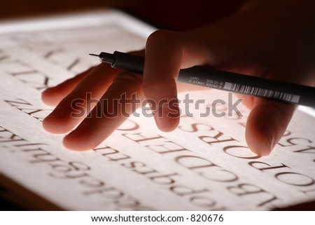 A hand working with a marker on a light table. - stock photo