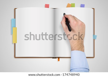 A hand writing down info to book - stock photo
