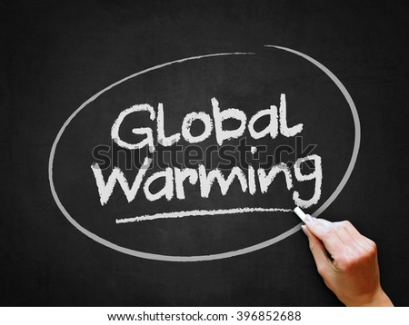 A hand writing 'Global Warming' on chalkboard. - stock photo