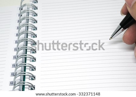 A hand writing in notebook - stock photo