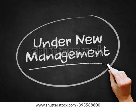 A hand writing 'Under New Management' on chalkboard. - stock photo