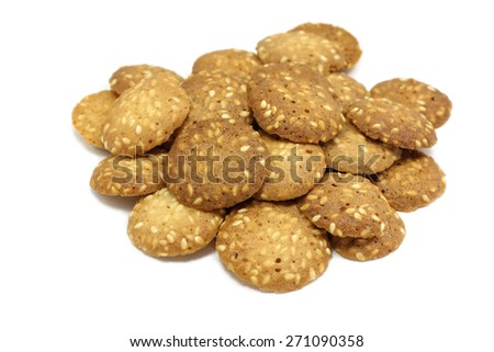a handful of biscuits with sesame seeds on a white background - stock photo