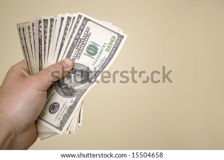 A handful of cash isolated over a gold background.