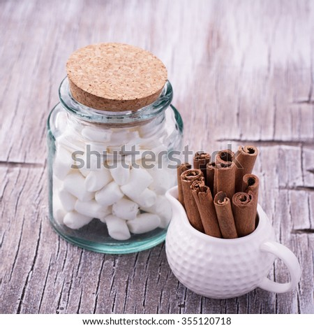 A handful of cinnamon sticks in a white ceramic jar with creamer and marshmallow for winter hot drink on a light wooden background. selective Focus - stock photo