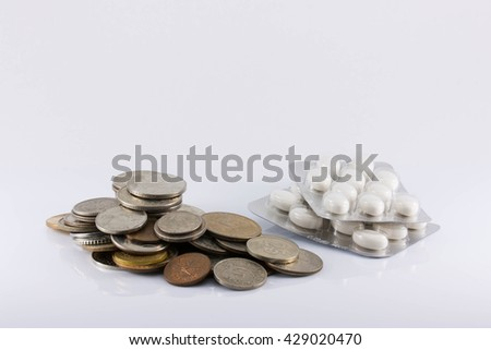 a handful of coins and pills on white background. The increase in drug prices, the rising cost of pills, inflation, crisis, isolated - stock photo