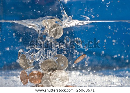 A handful of coins dropping into a pool of water. - stock photo