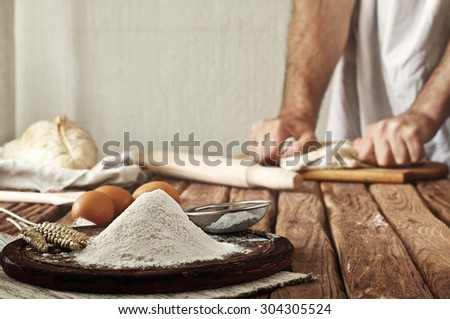 A handful of flour on a rustic kitchen. Against the background of men's hands knead the dough. Ingredients for cooking flour products or dough (bread, muffins, pie, pizza dough). Copy space - stock photo
