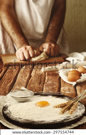 A handful of flour with egg yolk and ears of wheat on the wooden desk. Against the background of men hands knead the dough. Ingredients for cooking flour products (bread, muffins, pie, pizza dough) - stock photo