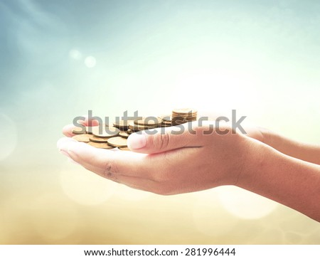 A handful of golden coins in the palm of a hand over blurred beautiful sunset background. Money coin concept. - stock photo