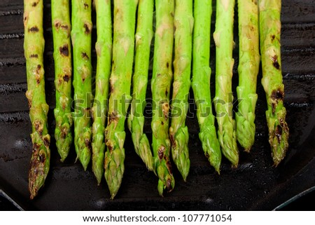 a handful of green asparagus cooking and steaming  on grill plate - stock photo