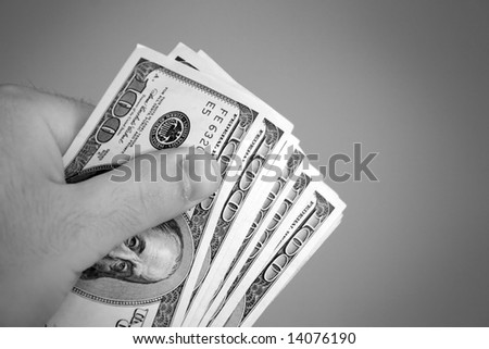 A handful of one hundred dollar bills in black and white.