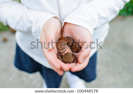 A handful of pennies rest in a girl's cupped hands. - stock photo