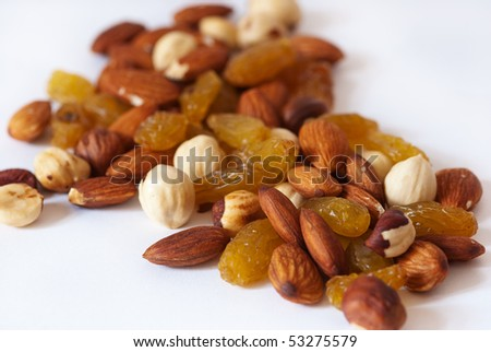 A handful of trail mix of almonds, hazelnuts, and raisins - stock photo