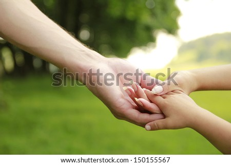 a hands of father, mother and child outdoors