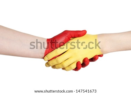 a handshake between a yellow and a red painted hand isolated
