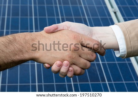 A handshake in front of photovoltaic solar energy panels
