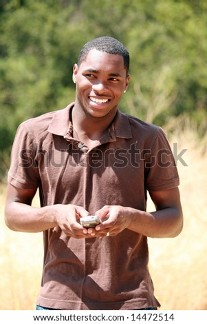 a handsome african american man smiles and responds while he text messages on his cell phone - stock photo