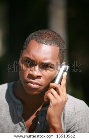 a handsome african american man talks on his cell phone