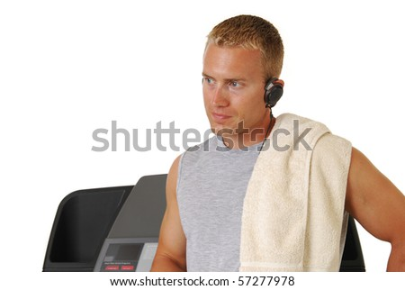 A handsome athletic man leaning against a treadmill - stock photo