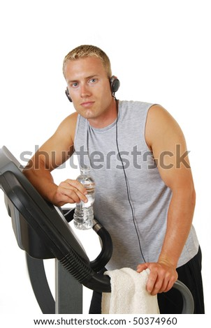 A handsome athletic man on a treadmill wearing headphones - stock photo