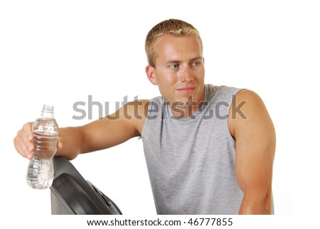 A handsome athletic man resting on a treadmill after a workout - stock photo