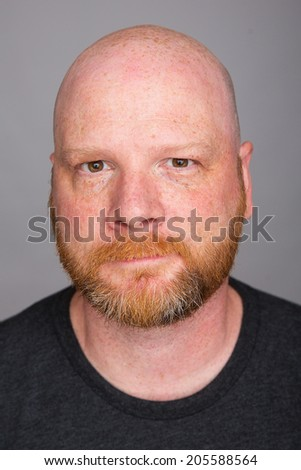 A handsome bald man with a red haired beard - stock photo