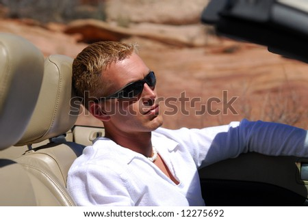 A handsome blond man driving a sports car in the southwest region - stock photo