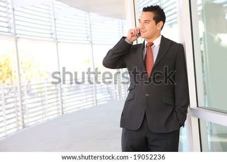 A handsome business man on the phone at office building - stock photo