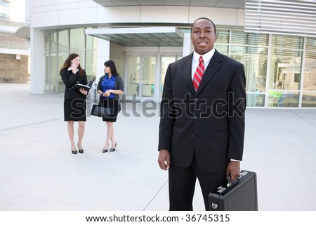 A handsome business man outside  office with coworkers in background