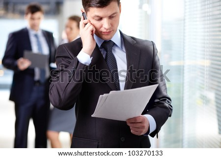 A handsome businessman calling by the phone in working environment