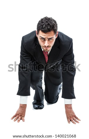 a handsome businessman in starting position ready to run a race - stock photo