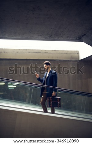 A handsome businessman using his smart phone while heading up to the office. - stock photo