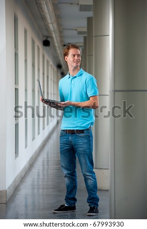 A handsome college guy holding a laptop and looking away on campus.  20s tall male caucasian British model.