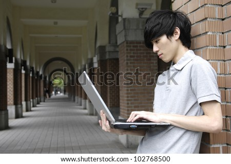 A handsome college student holding laptop on campus. - stock photo