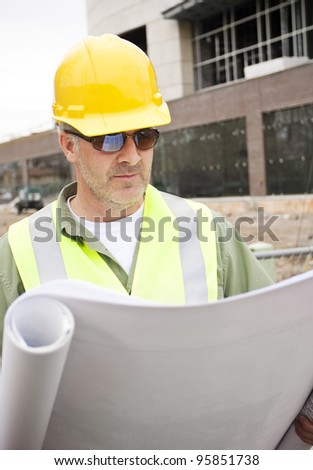 A handsome construction foreman looking at building blueprints - stock photo
