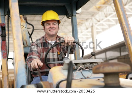 A handsome construction worker driving a bulldozer on a construction site. - stock photo