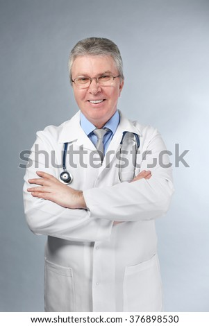 A handsome doctor with crossed arms standing on grey background - stock photo