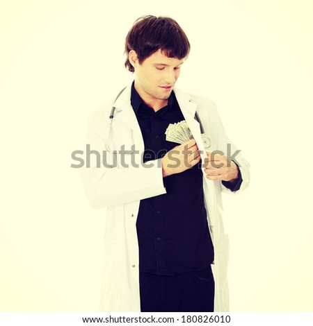 A handsome doctor with money - stock photo