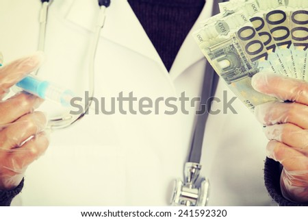 A handsome doctor with money and syringe. - stock photo