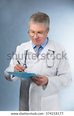 A handsome doctor with stethoscope and clipboard standing on grey background
