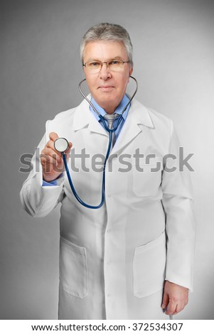 A handsome doctor with stethoscope standing on grey background