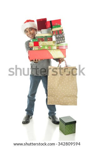 A handsome elementary boy delightedly carrying a large stack of wrapped Christmas gifts.  On a white background. - stock photo