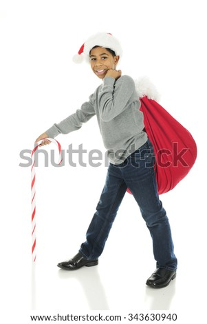 A handsome elementary boy wearing a Santa hat with Santa's sack over his shoulder and a giant candy cane leading his way.  On a white background. - stock photo