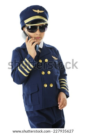 "A handsome elementary ""pilot"" in sunglasses talking on his flip-phone.  On a white background."
