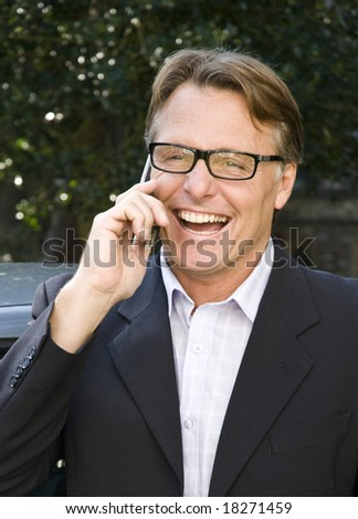 A handsome forties businessman is chatting on his cellphone and laughing