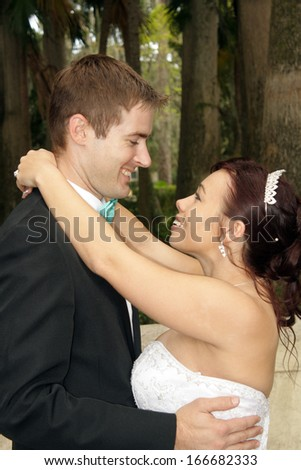 A handsome groom with his beautiful bride outdoors.