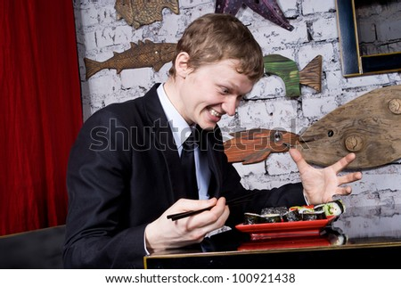 A handsome guy in the restaurant of the happy sushi - stock photo