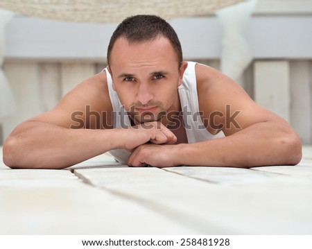 A handsome guy lying on the floor,at home - stock photo