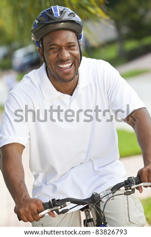 A handsome happy African American man with a big smile riding his bicycle outside - stock photo